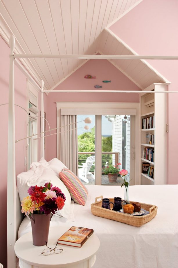 a bedroom with a white bed, pink walls and a matching sloping ceiling is such a cozy sleeping space