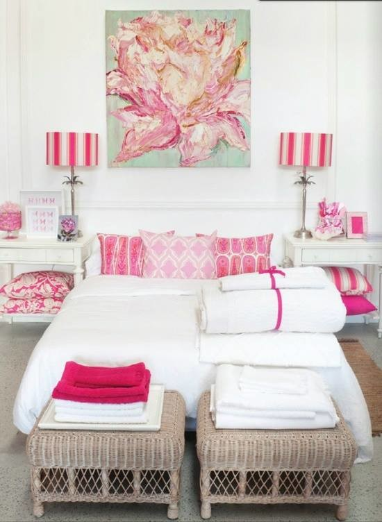 a big painting of a pink flower complements a white and pink bedroom perfectly