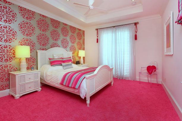 a pink floor area and a wall with pink patterns behind a white wooden bed