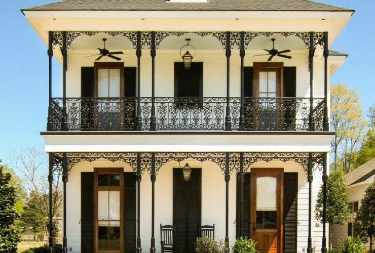 lanky wrought iron columns add a pleasant look to the porch of a two-story house